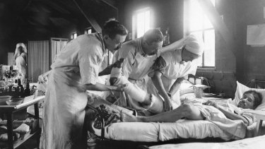 Medical staff apply a dressing to the leg of a wounded World War I French soldier at a mobile hospital south-west of Amiens.