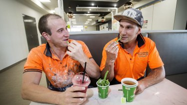 Construction workers Jeremy Krojs (left) and Darryl Piotrowski eating green beans and drinking a smoothie and green tea at Oliver's Real Food in Port Melbourne.