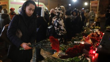A woman lays flowers at the well-known military choir's building in Moscow.