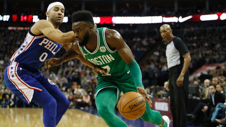Boston Celtics guard-forward Jaylen Brown, right, drives past Philadelphia 76ers guard Jerryd Bayless.