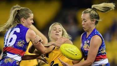 WA's Demi Okely is tackled by Bulldogs Katie Brennan and Lauren Arnell during an exhibition match