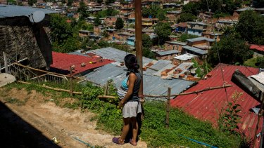 Yusdelis, 19 years old and eight months pregnant, stands near her house in a slum area of Los Teques, in Miranda state, outside Caracas.
