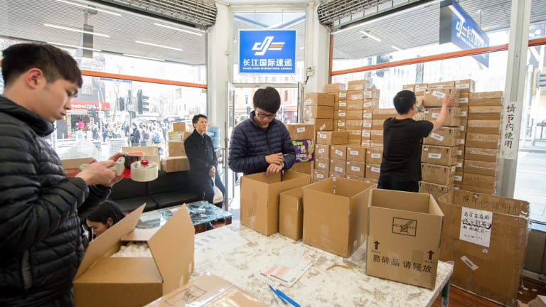 Workers and customers at the Chang Jiang International Express store on Swanston Street in  Melbourne package up Australian goods for export to China.