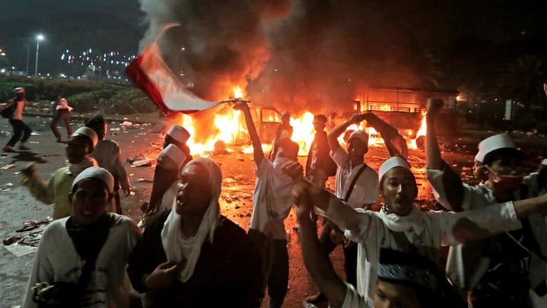 Muslim protesters chant slogans near burning police trucks during the clashes.