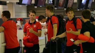 Protest? Western Sydney Wanderers team members wait for their boarding passes at the counter before their departure for Saudi Arabia.