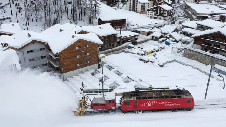 A snow blower on a train clears snow from the rail track in Zermatt, Switzerland.