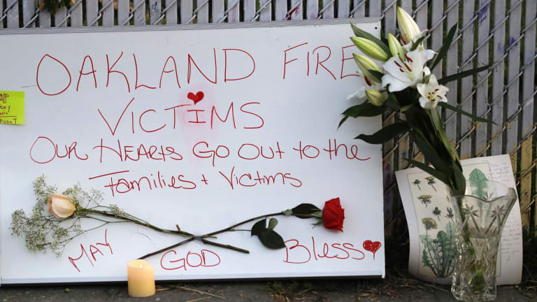 Signs and flowers adorn a fence near the site of a warehouse fire in Oakland, California.