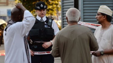 A police officer talks to local people at Finsbury Park after the attack.