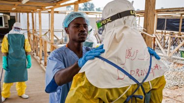 A health care worker prepares a colleague's protective gear at an Ebola virus clinic operated by the International Medical Corps in Makeni, Sierra Leone.