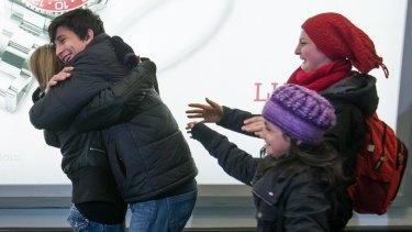 Shergo Kurdi hugs his aunt, Tima Kurdi, as his sisters, Ranim Kurdi, front right, and Haveen Kurdi, run to meet her as the family arrives in Vancouver.