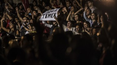 Supporters of Dilma Rousseff, suspended president of Brazil, cheer and hold a sign against Michel Temer in Rio de Janeiro.