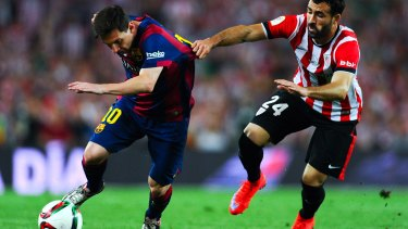 No holding him back:  Lionel Messi of FC Barcelona competes for the ball with Mikel Balenziaga.