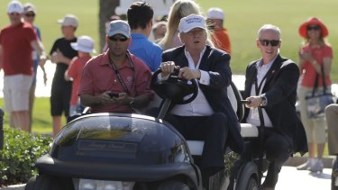 Donald Trump drives himself around the golf course in Doral, Florida.