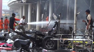 Firefighters try to extinguish the fire after a bomb hidden in a car exploded in southern Thailand in May.
