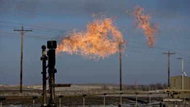 A gas flare burns near a crude oil site in North Dakota, US.