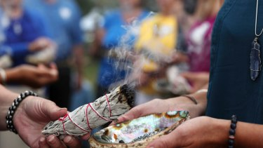 Volunteers take part in a Native American spiritual burning of sage during the memorial service for Justine Damond at Lake Harriet in Minneapolis.