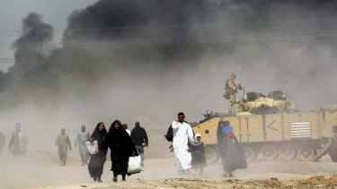 The war: Iraqis pass by a British tank as they flee Basra in 2003.