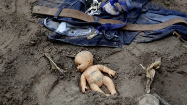 A doll and clothing lie in the mud as rescue workers continue to search the site of the deadly mudslide in Cambray, a suburb of Santa Catarina Pinula.