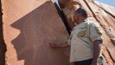 Senior cultural ranger at Murujuga National Park, Dallas Fredericks, stands next to a rock carving of a thylacine (Tasmanian tiger).