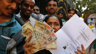 An woman shows discontinued Indian currency notes and a photocopied ID card as she queues outside a bank. Modi's experiment has upset many.