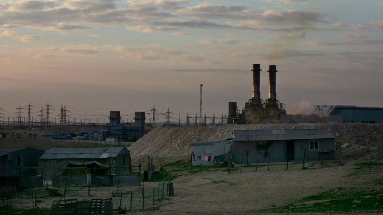 Bedouin homes sit in front of an Israeli power plant at Wadi al-Naam, near Beersheba.