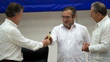 Colombian President Juan Manuel Santos, left, hands the bullet pen to FARC Commander Timochenko, centre, as Cuban President Raul Castro watches.