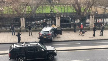 People stand near a crashed car and an injured person lying on the ground, right, on Bridge Street near the Houses of Parliament in London on Wednesday.