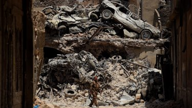 An Iraqi Special Forces soldier walks in front of a wall of debris on a road in West Mosul, Iraq.
