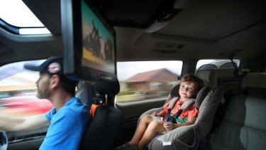 Orlando Moodley, 3, enjoys watching <i>Ice Age</i> on a DVD player while his dad Paul concentrates on driving.