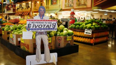 """A sign in Spanish which translates, """"Don't Lose Your Voice, Vote!"""" is displayed near a polling place in a Cardenas supermarket in Las Vegas."""