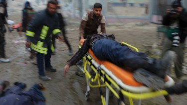 Syrian Civil Defence workers carry a victim on a stretcher after strikes on the Jub al-Quba district in Aleppo where people were killed in the streets.