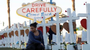 Cece Navarrette sits near a cross for her cousin, Bailey Schweitzer, who was among those killed during the mass shooting in Las Vegas.