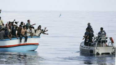 Armed Forces of Malta marines toss bottles of water to a group of about 180 asylum seekers south-west of Malta.