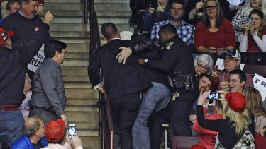 Hamid is removed by two officials as Republican presidential candidate Donald Trump speaks during a campaign stop in South Carolina.