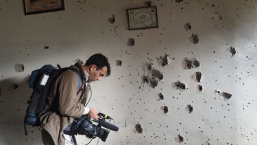A Pakistani camera man shoots video in front of a bullet-riddled wall at the arm- run school a day after an attack by Taliban militants in Peshawar.