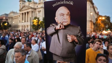 "A man holds a banner depicting Hungarian Prime Minister Viktor Orban which reads ""mini-prime minister"" during a protest against Orban's policies in Budapest."