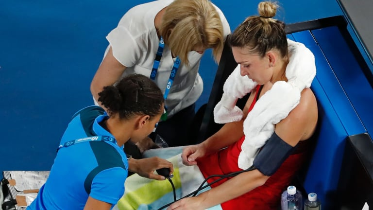 The heat and a long tournament take their toll on Simona Halep as she receives treatment from medical staff.
