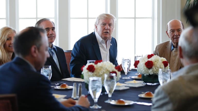 President Donald Trump, centre, meets staff at the Trump National Golf Club in Sterling, Virginia.