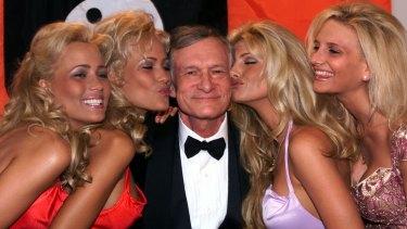Hugh Hefner basks in the kisses of his playmates in Cannes, in 1999.