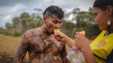 FARC rebel couple Camila gives her boyfriend Cristobal an ice cream as he plays soccer in the mud following a guerrilla conference in the remote Yari plains on Sunday.