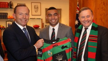 Former prime minister Tony Abbott presents a South Sydney NRL Jersey to Nathan Merritt.