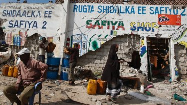 A Somali man sits next to the remains of his partially destroyed fuel shop near the scene of a suicide car bomb attack.