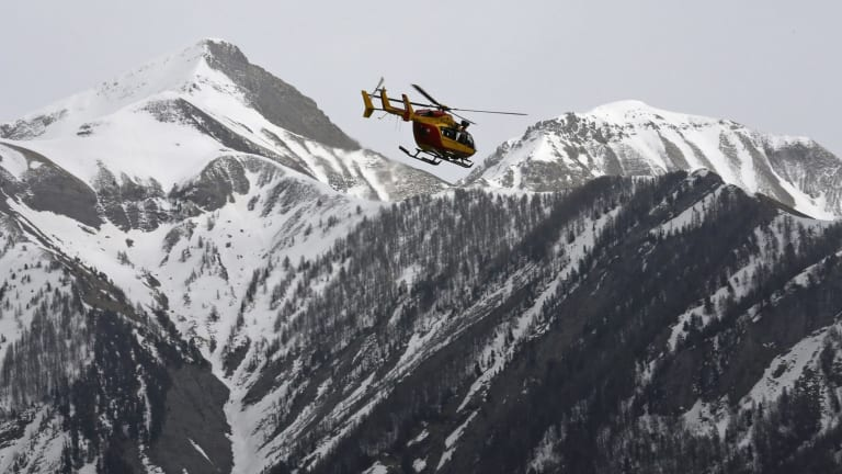 A rescue helicopter from the French Securite Civile flies over the French Alps following the crash of an Airbus A320.