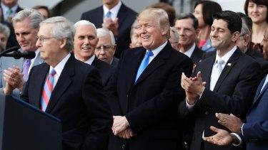 President Donald Trump listens with House Speaker Paul Ryan celebrating the passage of the tax cut legislation.