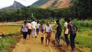 Sri Lankans walk on mud after a massive landslide at Aranayaka in Kegalle District.