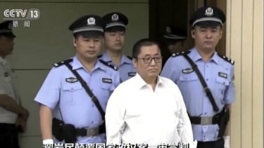 Zhai Yanmin is escorted by policemen as he arrives at the Tianjin court.