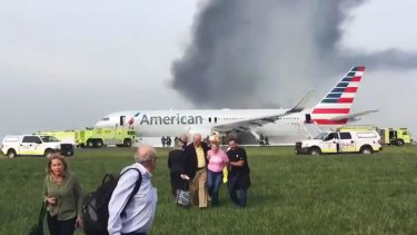 Passengers walk away from the burning American Airlines jet at O'Hare Airport.