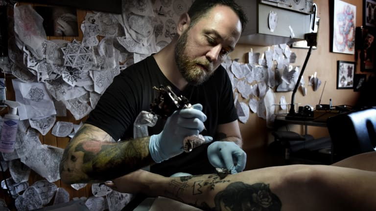 Artist and tattooist artist Leslie Rice applying a vintage-inspired image to Charlie Tapper.