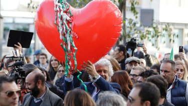 Five Star Movement leader Beppe Grillo holds a heart-shaped balloon adorned with strips in the colours of the Italian flag during a demonstration to support the vote NO in Rome.
