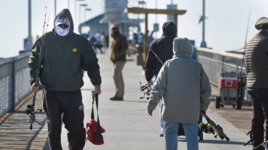 Angler Ron White is bundled up against the cold as he walks down a fishing pier in Fort Walton Beach, Florida.